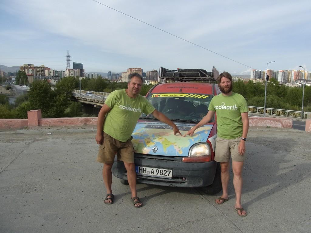 Team Fritz vor der Skyline von Ulan-Bator, auf das Ziel in der Karte zeigend
